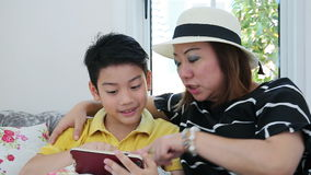 Happy asian boy and his mom playing games on smart phone stock footage