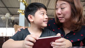 Happy asian boy and his mom playing games on smart phone stock video