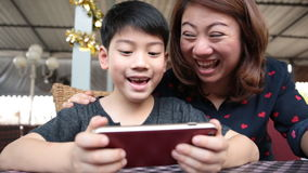 Happy asian boy and his mom playing games on smart phone stock video footage