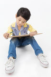 Happy Asian boy holding a art board. Happy Asian little artist boy holding a art board  on gray background Royalty Free Stock Photo