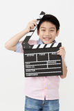 Happy asian boy holding clapper board in hands. Cinema concept Stock Image