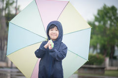 Happy asian boy holding colorful umbrella playing in the park stock image