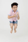 Happy asian boy is jumping at studio. Stock Photos