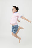 Happy asian boy is jumping at studio. Stock Images