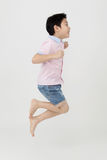 Happy asian boy is jumping at studio. Royalty Free Stock Images