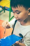 Happy asian boy painting blue color on artwork with paintbrush. royalty free stock photos