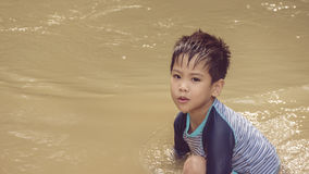 Happy asian boy playing in river Stock Image