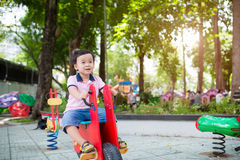 Happy asian boy playing seesaw at the playground in the park Royalty Free Stock Images