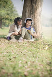 Happy Asian boy reading a book outdoor, Stock Images