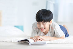 Happy Asian boy reading story book on the bed. Happy Asian boy is reading story book on the bed Stock Photos