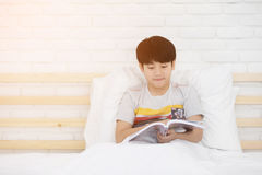 Happy Asian boy reading story book on the bed. Happy Asian boy is reading story book on the bed Stock Images