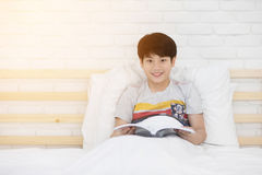 Happy Asian boy reading story book on the bed. Happy Asian boy is reading story book on the bed Royalty Free Stock Images