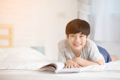 Happy Asian boy reading story book on the bed. With sun light in morning Stock Photos