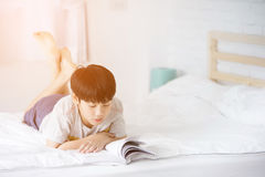 Happy Asian boy reading story book on the bed. With sun light in morning Stock Photography