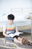 Happy Asian boy reading story book near white bed Stock Image