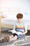 Happy Asian boy reading story book near white bed Stock Photography