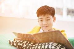 Happy Asian boy reading story book on the sofa Royalty Free Stock Photo