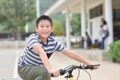 Happy Asian boy riding a bike outdoor. Happy Asian boy riding a bike in the park outdoor Stock Image
