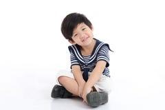 Happy asian boy sitting on white background Royalty Free Stock Photo