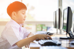 Happy asian boy in student uniform using computer at school . Stock Images