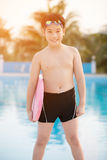 Happy asian boy in swimsuit coming up the pool Stock Photos