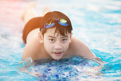 Happy asian boy in swimsuit coming up the pool Stock Photo