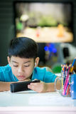 Happy asian boy usins cellphone at home Stock Images