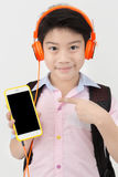 Happy Asian boy ware headphone and holding the cell phone . Royalty Free Stock Photos