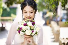 Happy asian bride with flowers. Beautiful and happy young asian bride wearing bridal veil holding a bunch of flower Royalty Free Stock Photo