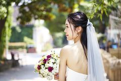 Happy asian bride with flowers. Beautiful and happy young asian bride wearing bridal veil holding a bunch of flower, rear view Royalty Free Stock Images