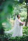 Happy Asian bride. In a long veil looking up Stock Photography