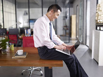 Happy asian business executive working in office Stock Images