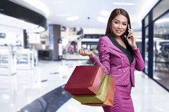 Happy asian business female making call while holding shopping b Stock Photo
