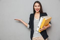 Happy asian business woman with folders holding copyspace on palm. Happy asian business woman with folders holding copyspace on the palm and looking at the Royalty Free Stock Photo