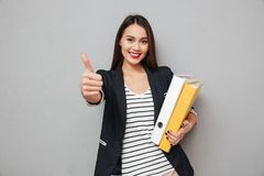 Happy asian business woman holding folders and showing thumb up. While looking at the camera over gray background Royalty Free Stock Images