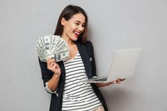 Happy asian business woman holding money and laptop computer. Over gray background Royalty Free Stock Image