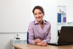 Happy Asian business woman with laptop in office Royalty Free Stock Image