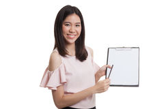 Happy Asian business woman point to clipboard with pen. Royalty Free Stock Images