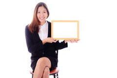 Happy asian business woman sitting and holding banner on white b Stock Photo