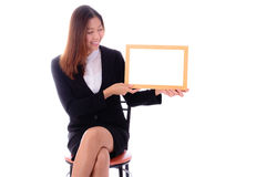 Happy asian business woman sitting and holding banner on white b Stock Photos