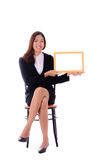 Happy asian business woman sitting and holding banner on white b Royalty Free Stock Image