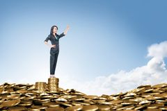 Happy asian business woman standing on the peak of coin pile royalty free stock photo