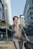 Happy Asian business woman talking on phone and walking on stree Royalty Free Stock Images