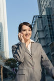 Happy Asian business woman talking on phone and walking on stree Royalty Free Stock Image