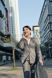 Happy Asian business woman talking on phone and walking on stree Stock Photos