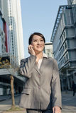 Happy Asian business woman talking on phone and walking on stree Stock Photo