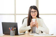 Happy Asian business women smiling and drinking coffee on laptop Stock Image