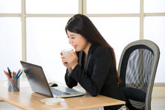 Happy Asian business women working and drinking coffee on laptop Stock Photo