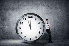 Happy asian businessman lean back on the clock with deadline tim. E for paying tax. Goods and Services Tax concept Royalty Free Stock Image