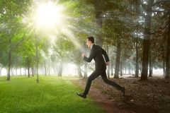 Happy asian businessman running on summer field Royalty Free Stock Images